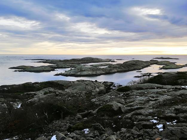 Mar cercado por rochas cobertas de ramos sob um céu nublado durante o pôr do sol na noruega