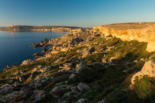 Mar cercado por rochas sob a luz do sol e um céu azul na costa noroeste, malta
