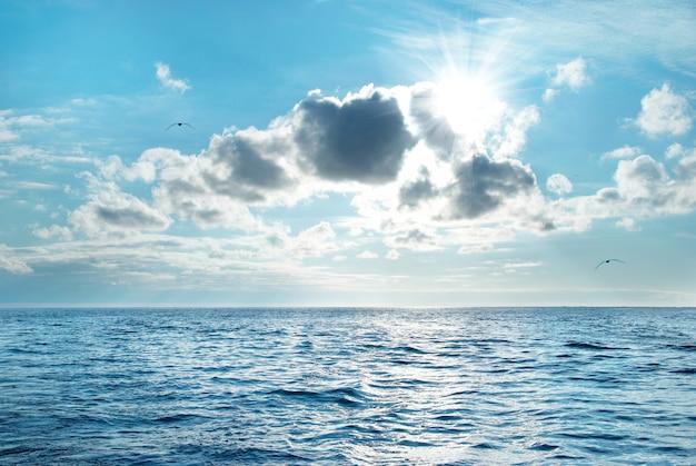Mar com água azul, céu e nuvens