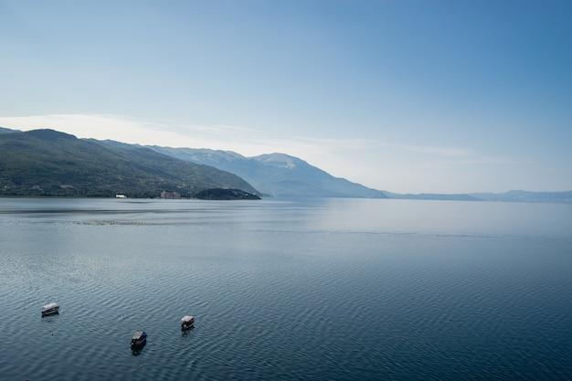 Mar com barcos rodeados por colinas cobertas de vegetação sob a luz do sol