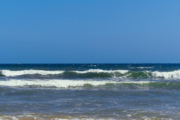 Mar com ondas em um dia nublado com kitesurfistas