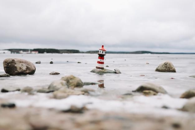 Mar congelado de inverno com farol decorativo. estilo de vida náutico. conceito de inverno, mar, viagens, aventura, feriados e férias. viagem em 2021