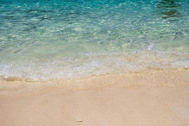 Mar de ondas de cristal com praia de areia
