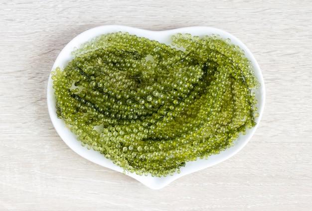 Mar de uvas no prato de coração em cima da mesa