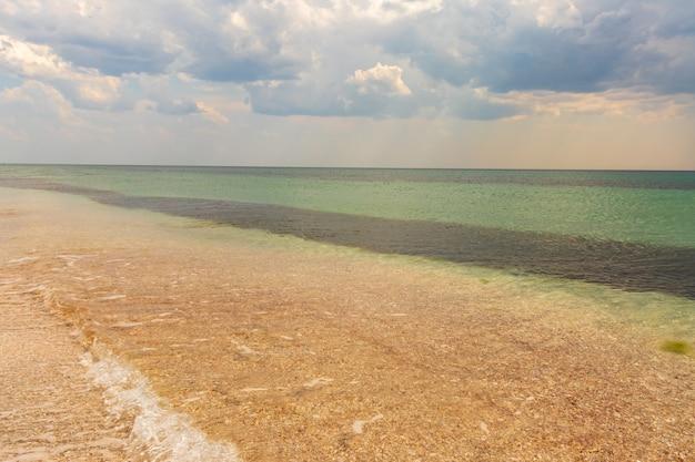 Mar de verão lindo de exótica praia tropical. verde esmeralda do mar e céu azul brilhante com nuvens com luz solar. vista do mar de verão, água turquesa do oceano, ilha idílica ou faixa de praia