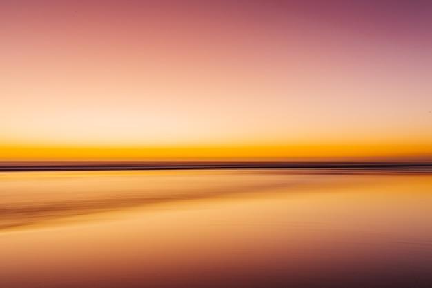 Mar durante um pôr do sol colorido com um efeito de movimento - uma imagem legal para papéis de parede e fundos