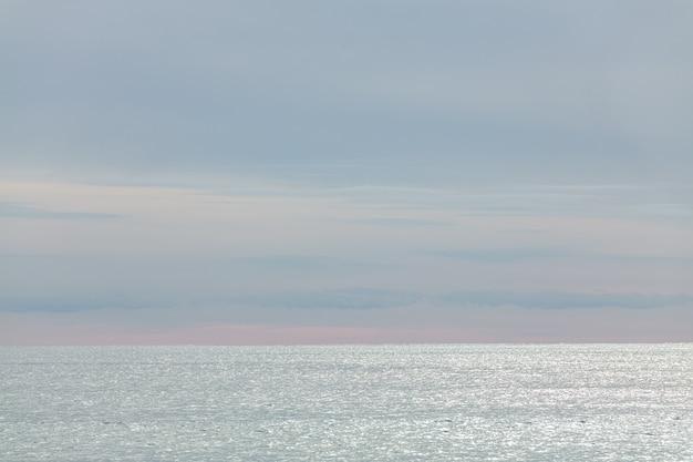Mar e céu de inverno com pequenas nuvens escuras