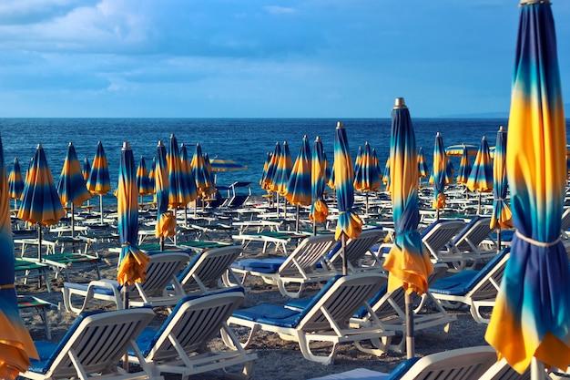 Mar ou oceano praia com espreguiçadeiras e guarda-sóis.