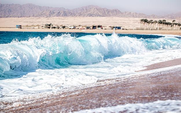 Mar revolto com ondas espumosas em tempo ensolarado. vista da costa com montanhas.
