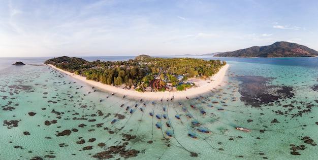 Mar tropical bonito com barcos de cauda longa e resort na ilha de lipe