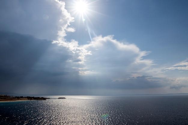 Mar tropical calmo sob nuvens de tempestade no horizonte