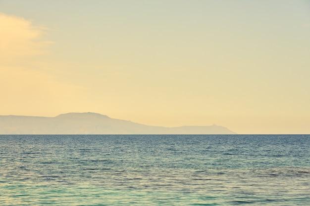 Mar tropical com ilhas rochosas no nevoeiro no horizonte como pano de fundo. copie o espaço.
