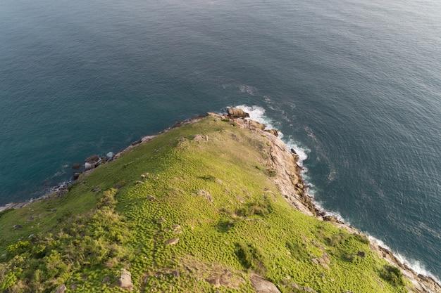Mar tropical com ondas batendo na beira-mar e alta montanha