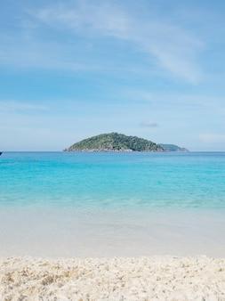 Mar tropical ondulado e calmo com pequenas ilhas no horizonte e nuvens brancas e fofas área de superfície do mar.