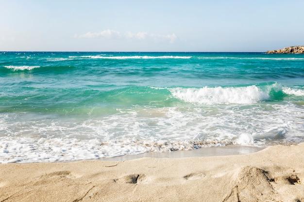 Mar turquesa com ondas espumosas em uma praia arenosa. turismo e viagens. espaço para texto.