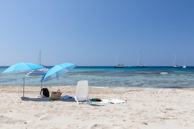 Mar turquesa e guarda-sóis em uma praia de areia branca em ibiza, espanha