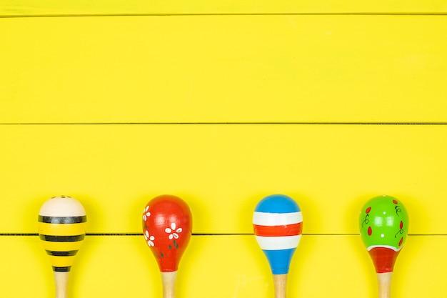 Maracas coloridas na placa de madeira amarela.