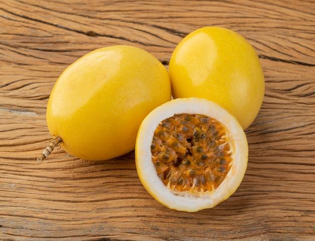 Maracujá com frutas cortadas sobre mesa de madeira.
