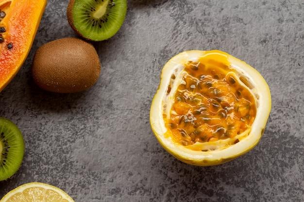 Maracujá cortado ao meio e outras frutas em fundo cinza