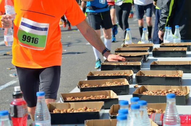 Maratona, corrida de estrada, corredores mão levando comida e bebida no ponto de refresco, esporte, fitness e conceito de estilo de vida saudável