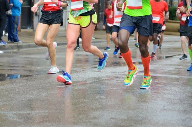Maratona corrida, muitos pés de corredores em corridas de automóveis, competição esportiva, fitness e conceito de estilo de vida saudável