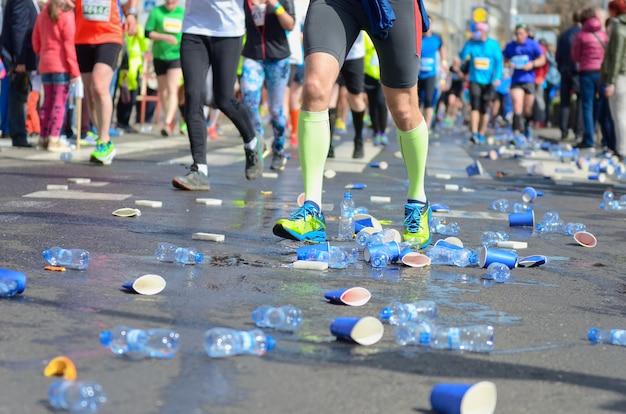 Maratona corrida, pés de corredores e copos de água de plástico na estrada perto do ponto de refresco, fitness e conceito de estilo de vida saudável