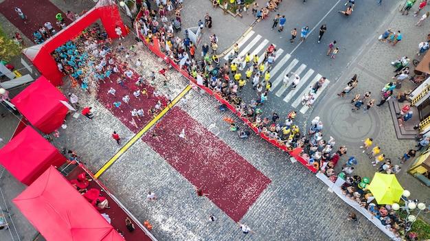 Maratona corrida, vista aérea da linha de partida e chegada com muitos corredores de cima, corridas de rua, competição esportiva, fitness e conceito de estilo de vida saudável