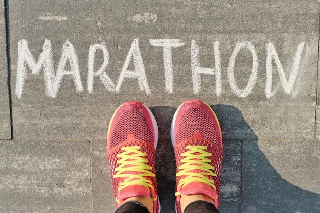 Maratona, escrita na calçada cinza com pernas de mulher no tênis