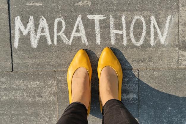 Maratona, escrita na calçada cinza com pernas de mulher, vista superior