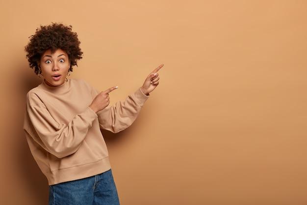 Maravilhada mulher de cabelos cacheados tem olhar curioso e excitado, mostra produto no espaço vazio, dá conselhos, vestida de moletom marrom, diz clique no link, isolado na parede bege