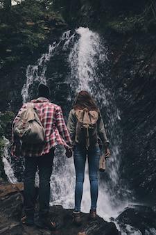 Maravilhado com a beleza da natureza. retrovisor de corpo inteiro de um jovem casal de mãos dadas perto da cachoeira