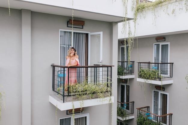 Maravilhosa garota caucasiana expressando felicidade enquanto posava no hotel. despreocupada mulher bronzeada encaracolada de vestido rosa.