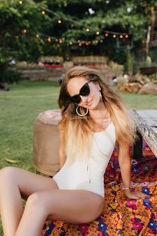 Maravilhosa garota caucasiana posando com um sorriso interessado enquanto tomava banho de sol na grama. mulher loira bonita em trajes de banho branco, deitado no chão no parque.