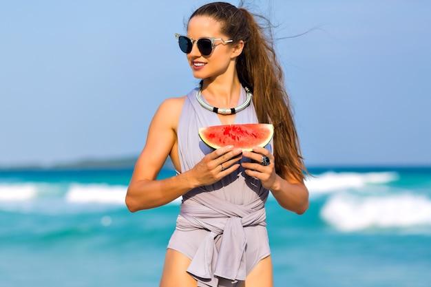 Maravilhosa garota de cabelos escuros em óculos de sol, posando no resort do mar nas férias de verão. retrato ao ar livre do modelo feminino moreno, segurando a melancia e olhando para o fundo do oceano.