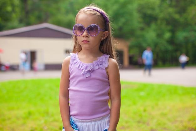 Maravilhosa garotinha em óculos de sol caminhando no parque de verão