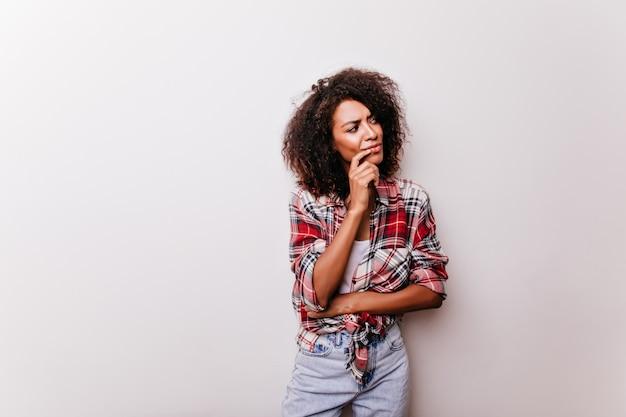 Maravilhosa jovem com cabelo castanho curto, pensando em algo. deslumbrante garota africana elegante.