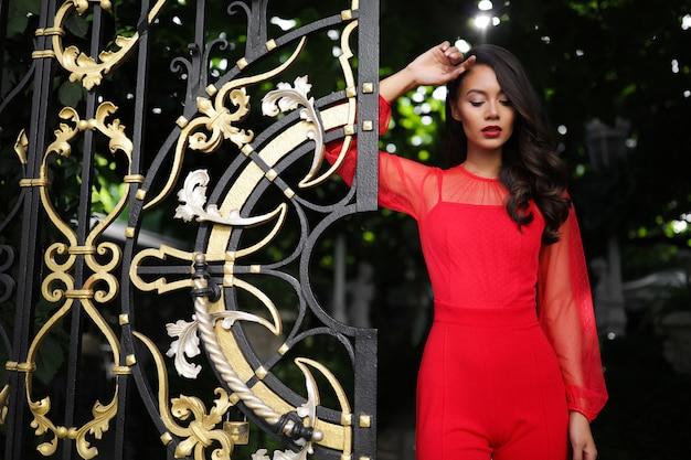 Maravilhosa jovem se encosta nos portões, estilo de cabelo, cacheado, maquiagem, blusa, calça, brilhante, senhora, glamourosa, moda, descolada, incrível, inesquecível