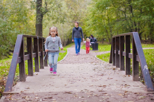 Maravilhosa menina andando ao ar livre com um pai e irmã de fundo
