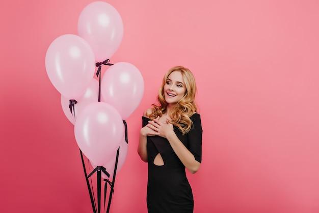 Maravilhosa mulher encaracolada com maquiagem na moda, posando com um sorriso surpreso na festa de aniversário. garota de cabelos louros magro em pé perto de balões rosa de hélio na parede brilhante.