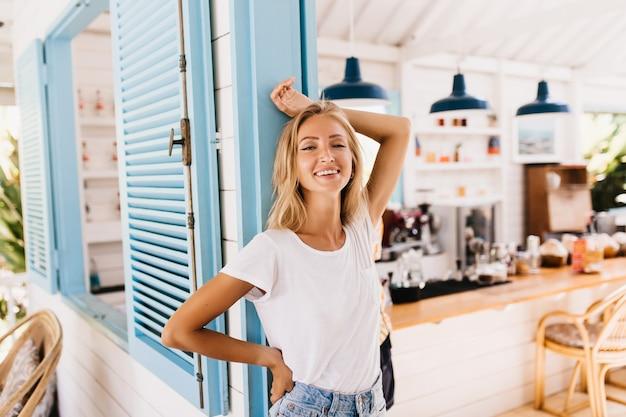 Maravilhosa mulher levemente bronzeada em jeans retrô, posando com um sorriso positivo.