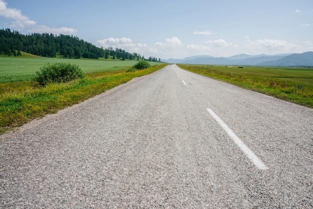 Maravilhosa paisagem cênica com longa estrada de asfalto através de campos verdes com vista para a montanha no horizonte. cenário verde vívido com estrada e prado sob o céu azul em dia ensolarado. asfalto brilhante na luz solar
