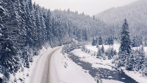Maravilhosa paisagem montanhosa de inverno, estrada de montanha coberta de neve com curvas e uma floresta no horizonte.