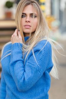 Maravilhosa senhora elegante com olhos azuis e maquiagem nude, posando para a câmera durante a sessão de fotos ao ar livre