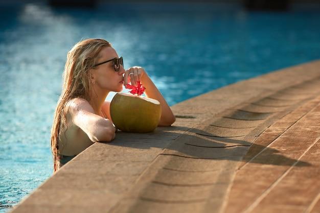 Maravilhosa turista feminina com cabelos loiros, relaxante na piscina com água azul clara e beber coco de palha. moça de óculos escuros e roupas de banho, passar dias ensolarados na água