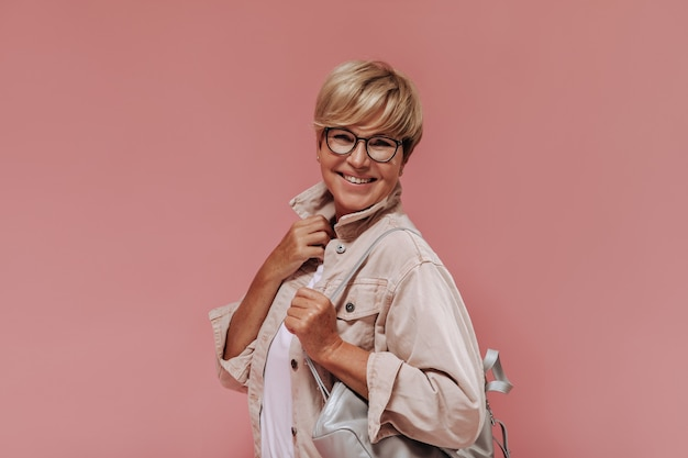 Maravilhosa velha com cabelo loiro e óculos elegantes de jaqueta bege e camiseta leve, sorrindo e posando com bolsa no fundo rosa.