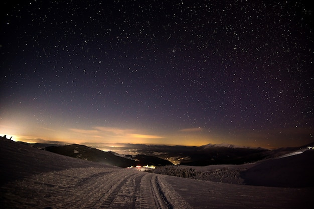 Maravilhosa vista noturna da estância de esqui com colinas e encostas tendo como pano de fundo a lua e o céu estrelado. o conceito de esportes de inverno e recreação ao ar livre. copyspace