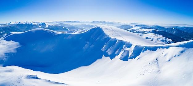Maravilhosas nevascas gigantes nas colinas nas montanhas cobertas de neve em um dia ensolarado de inverno gelado
