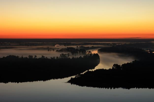 Maravilhoso amanhecer nebuloso fantasmagórico acima silhueta da ilha e do rio enevoado.