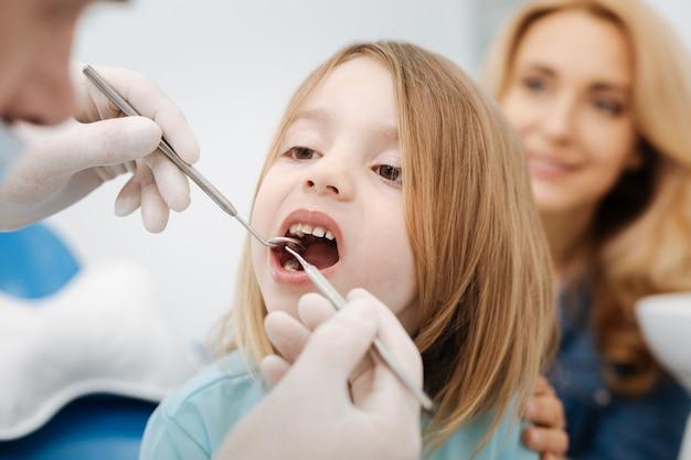 Maravilhoso e agradável médico amigável examinando os dentes de seus pequenos pacientes enquanto usa ferramentas especiais que proporcionam uma visão melhor