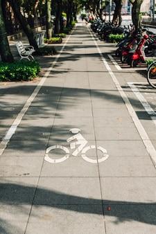 Marca da pista de bicicleta no passeio com luz e sombra das árvores em taipei, taiwan.